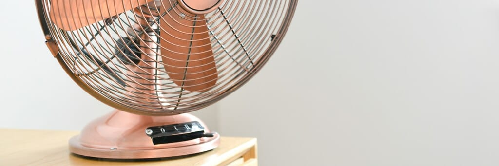 Rose gold colored traditional electric fan in a home.