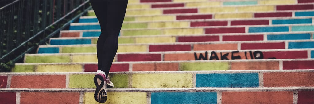 Woman running up colourful stairs